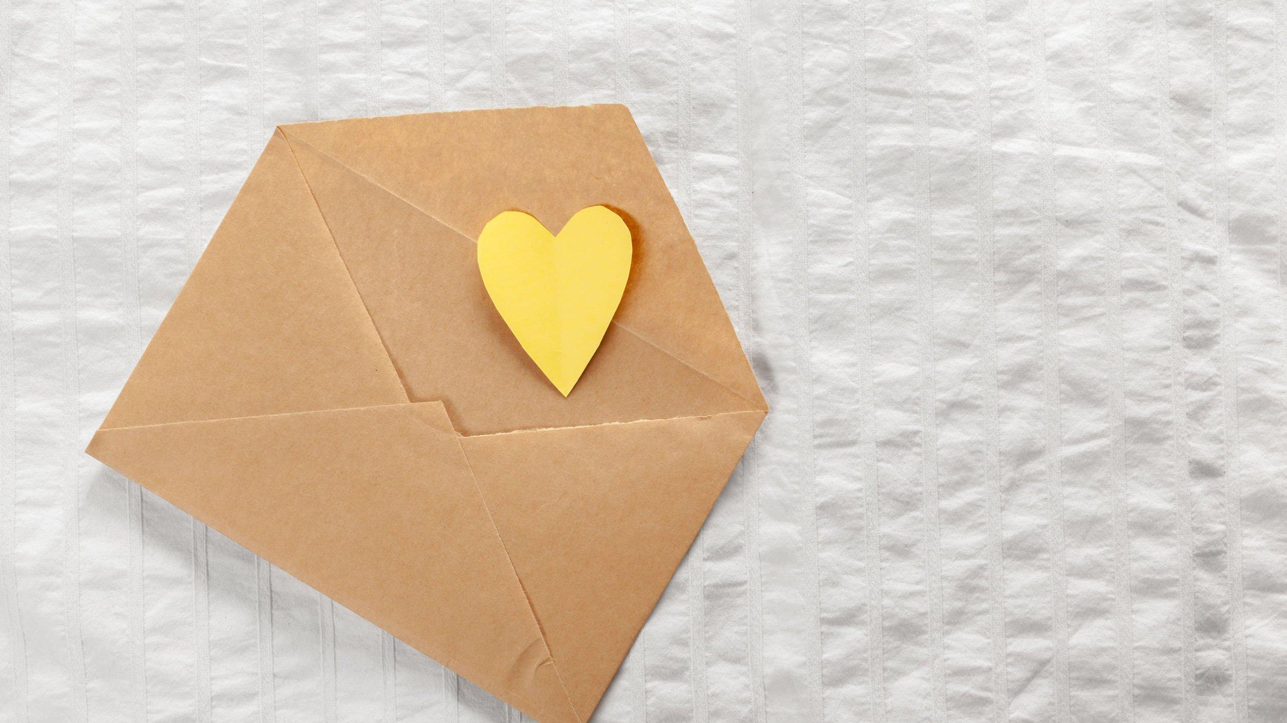 Envelope marrom aberto, com coração amarelo saindo dele, colocado sob mesa branca