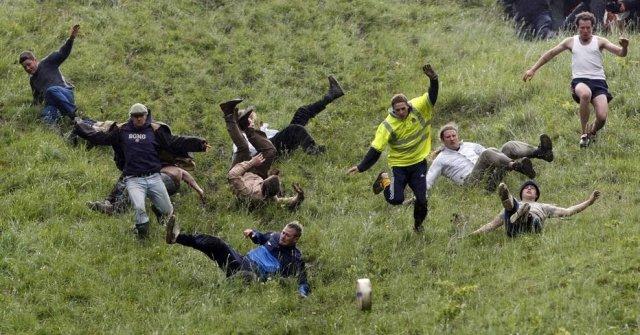 Pessoas correndo atrás de queijo em ladeira