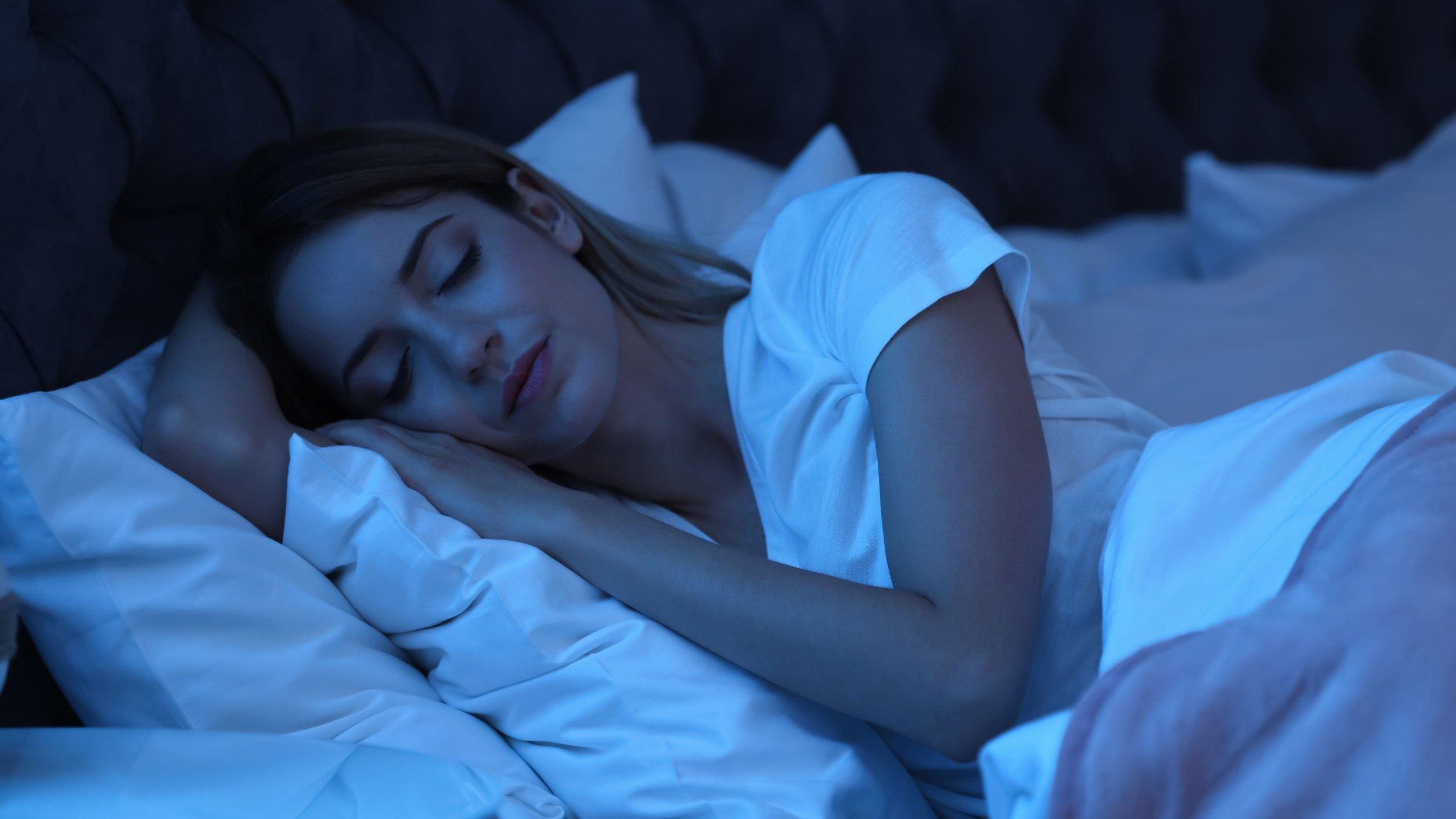 Mulher deitada em cama, dormindo