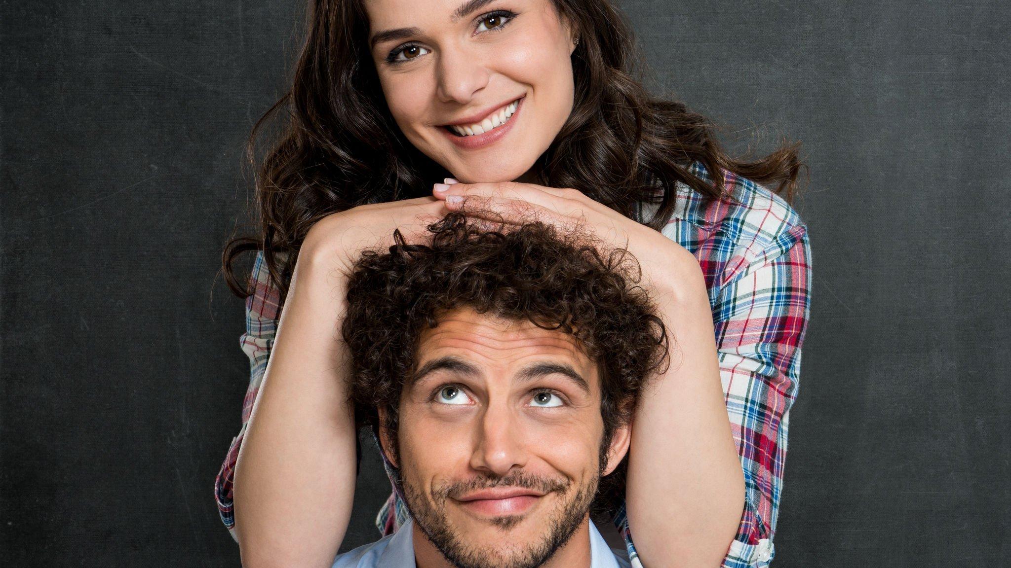 Homem e mulher sorrindo, mulher está se apoiando na cabeça do homem