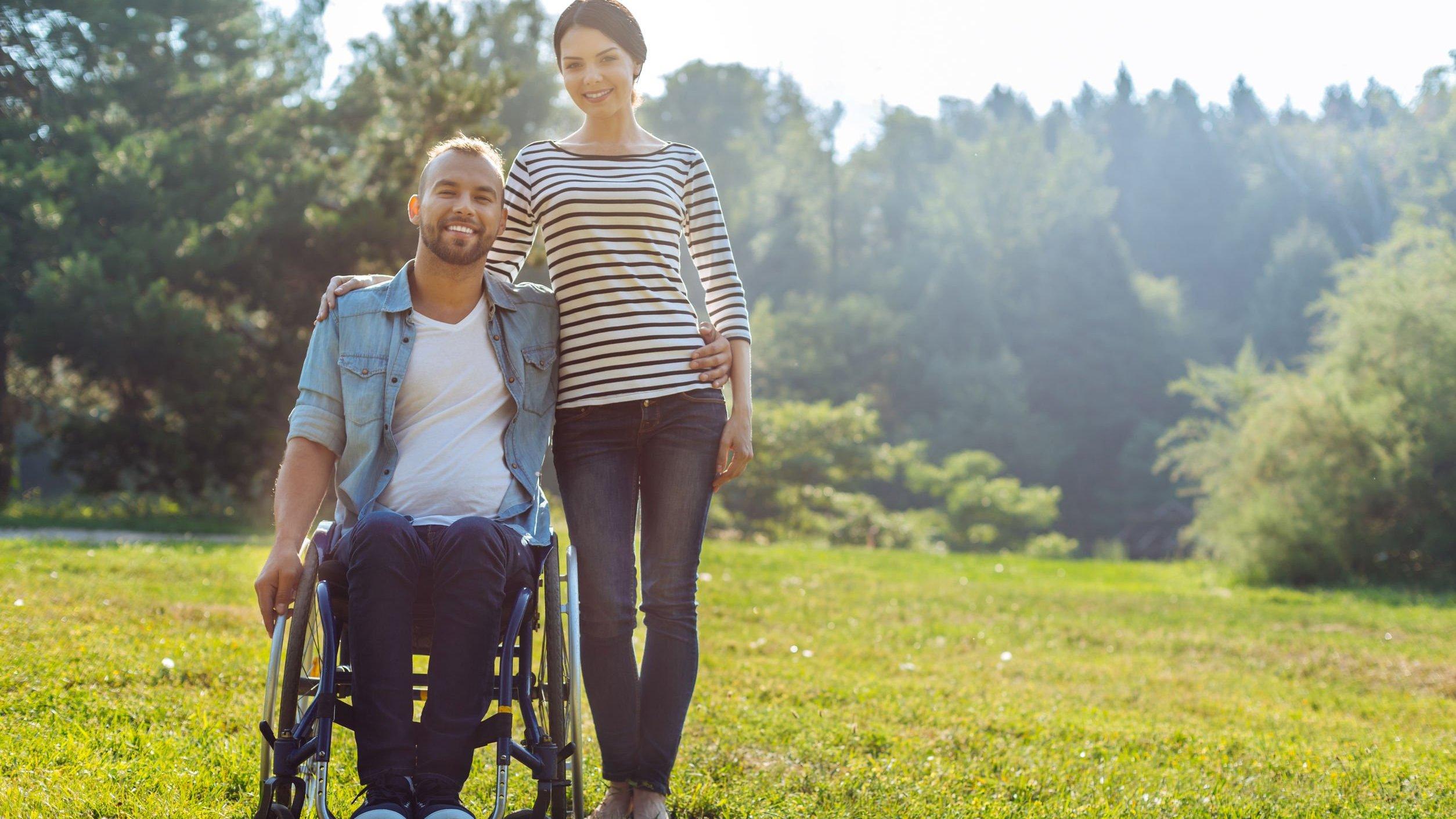 Homem em cadeira de rodas e mulher abraçada ao lado