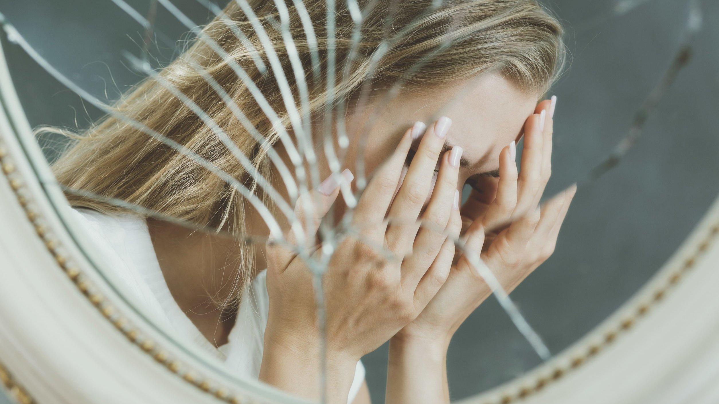 Reflexo em espelho quebrado de mulher cobrindo o rosto com as mãos