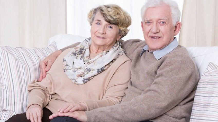 Homem e mulher idosos abraçados sorrindo