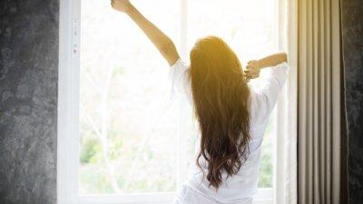 Mulher se espreguiçando após acordar em frente a janela