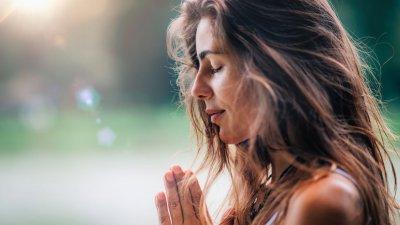 Mulher orando sentada segurando bíblia