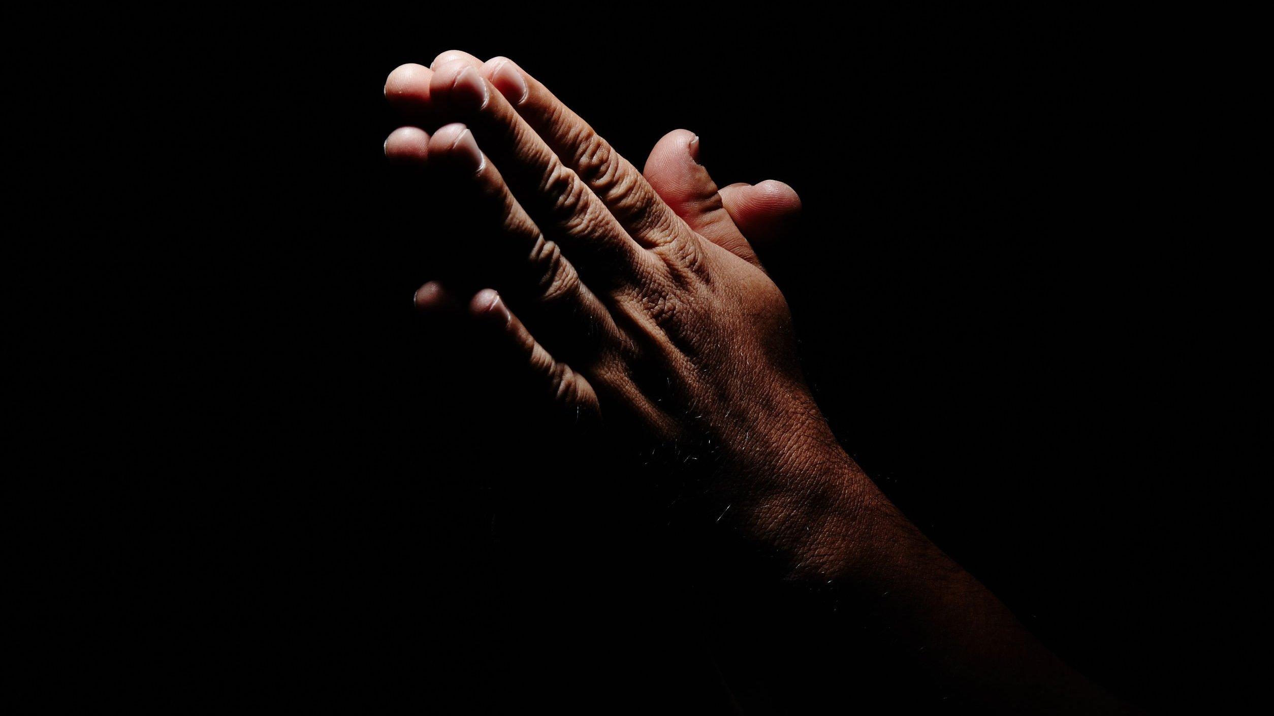 Mão de pessoa orando em frente de fundo preto