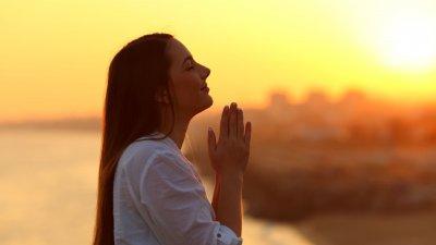 Mulher orando durante tarde ensolarada