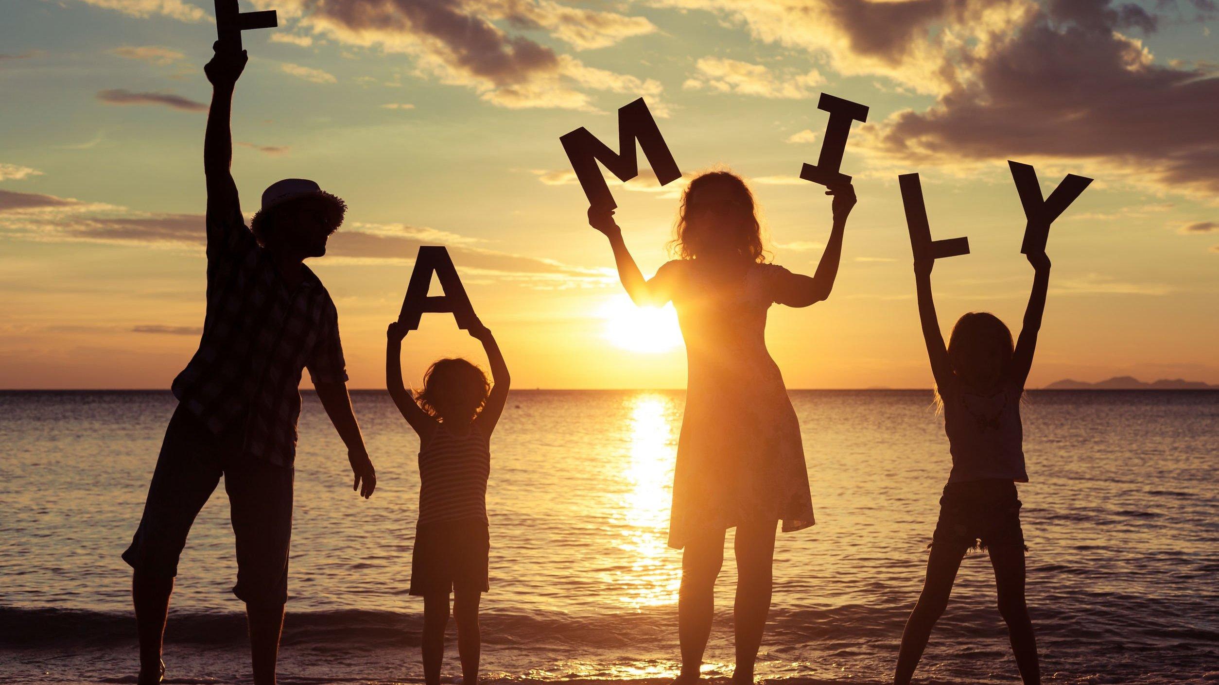 Silhueta de família segurando letras de madeira formando a palavra família em inglês