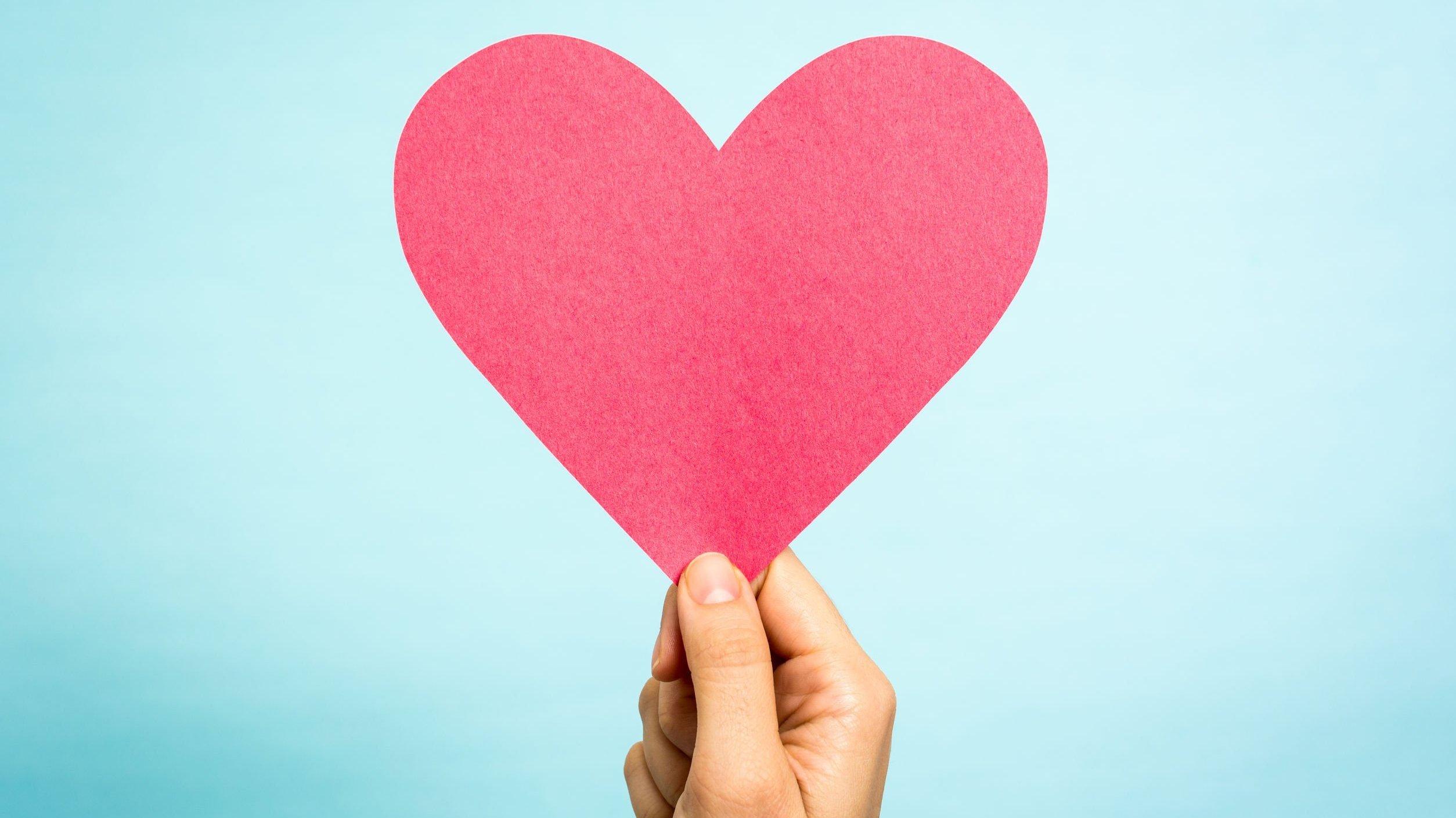 Mão de pessoa segurando coração de papel