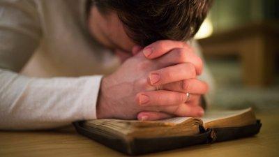 Homem orando apoiando-se em bíblia