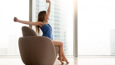 Mulher se espreguiçando sentada perto de janela de vidro mostrando dia ensolarado