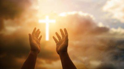 Mãos levantadas em direção ao céu, com uma luz em forma de cruz em meio as nuvens