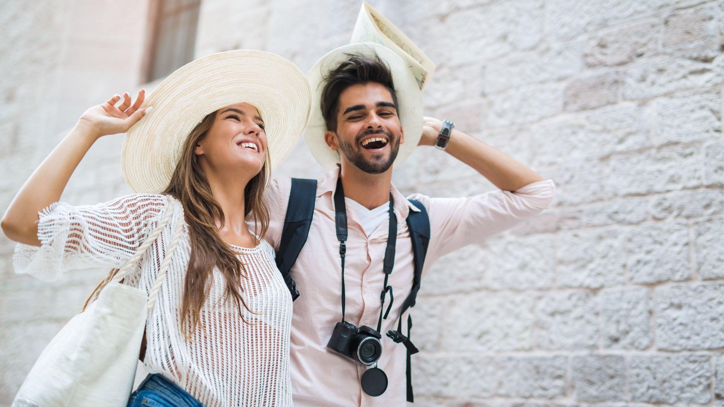 Homem e mulher sorrindo caminhando com os cabelos ao vento