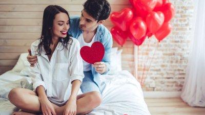 Casal sentado em cama sorrindo