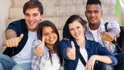 Adolescentes sorrindo e fazendo sinal de jóia com as mãos