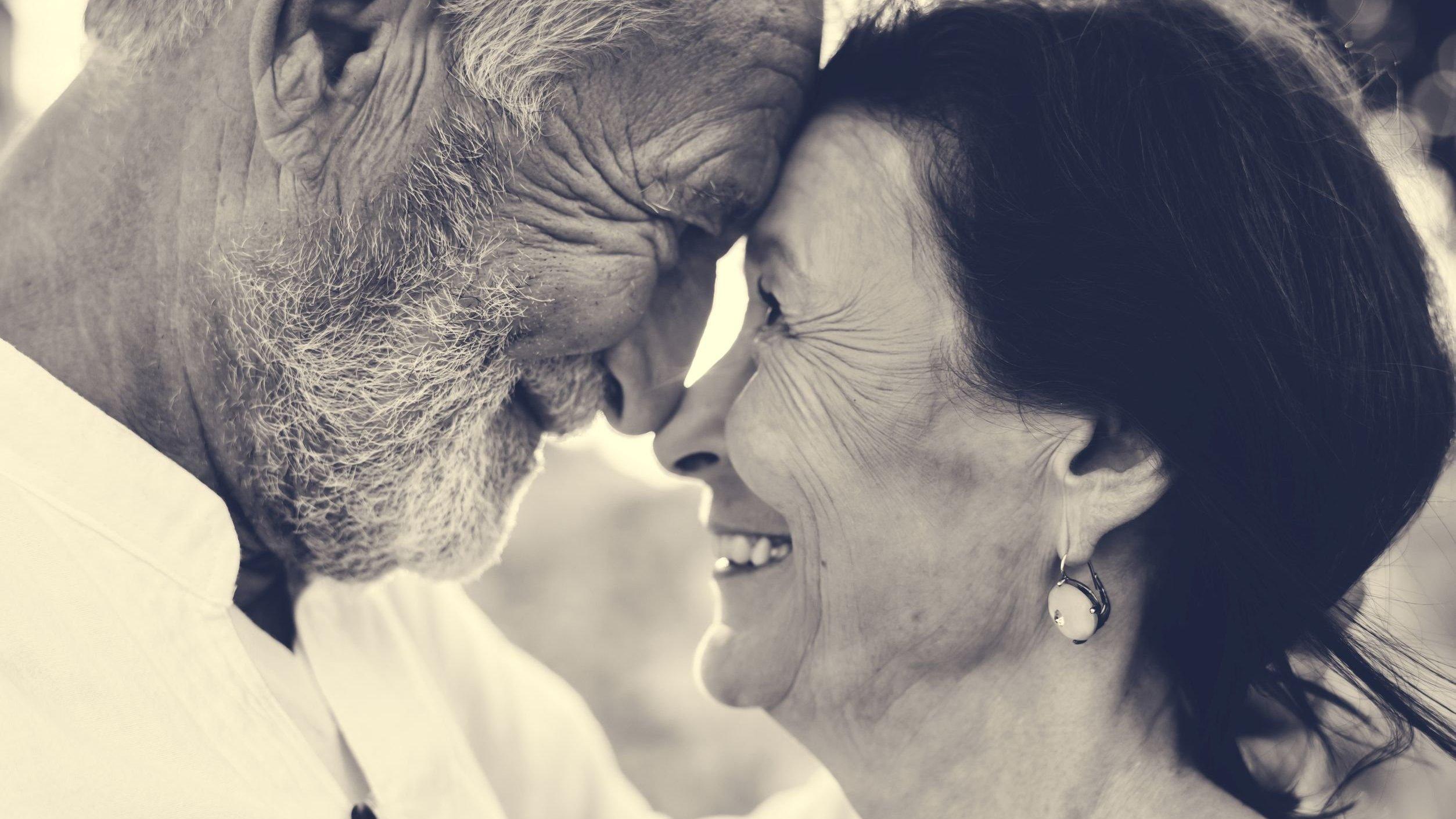 Casal de idosos sorrindo com o rosto um próximo do outro