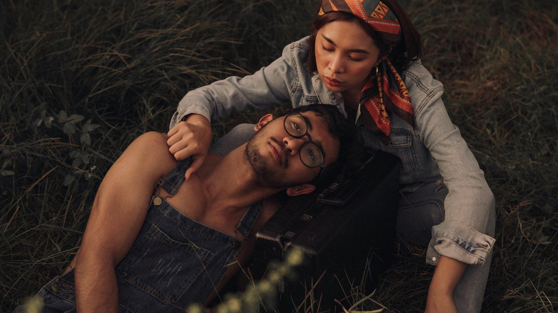 Homem deitado em grama, com mulher fazendo carinho no seu ombro