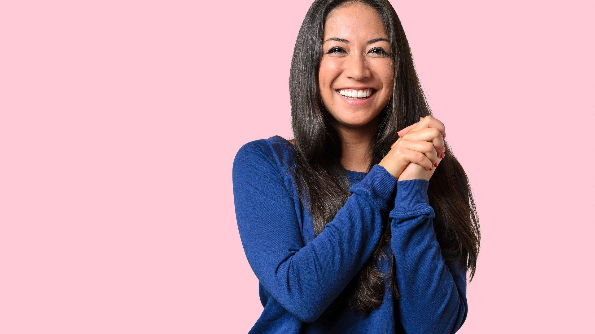 Mulher sorrindo, posando com as duas mãos juntas
