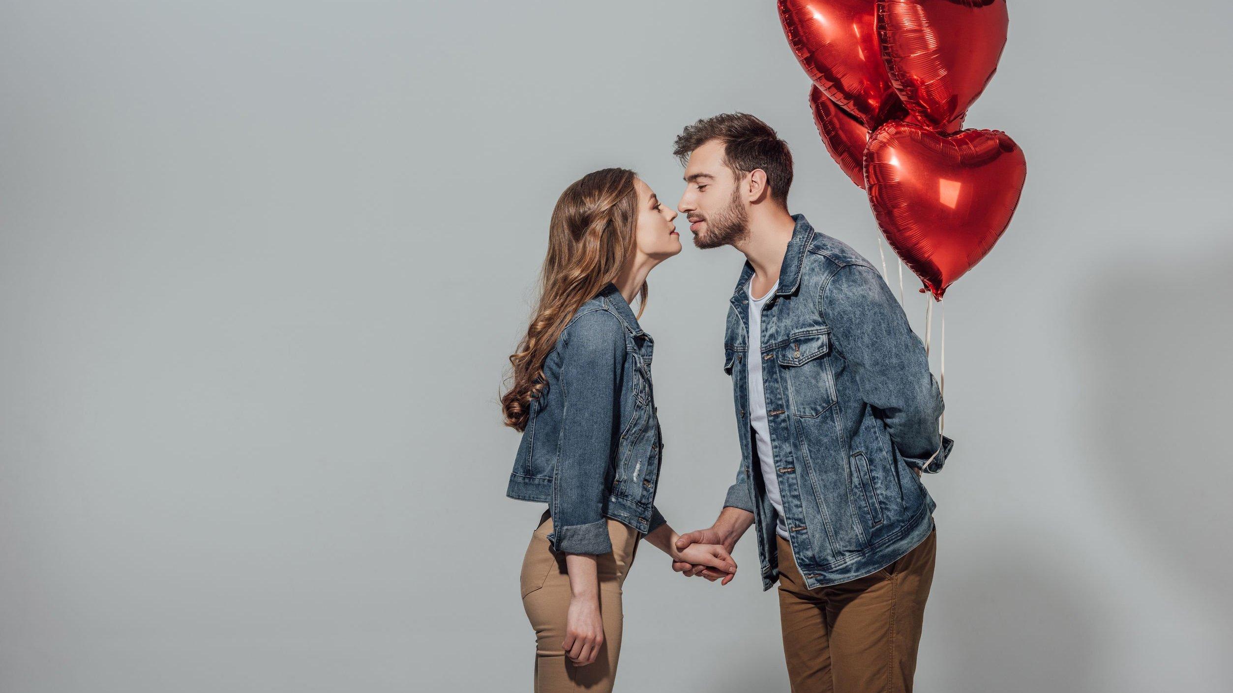 Homem segurando balão de corações com mão atrás das costas e beijando mulher