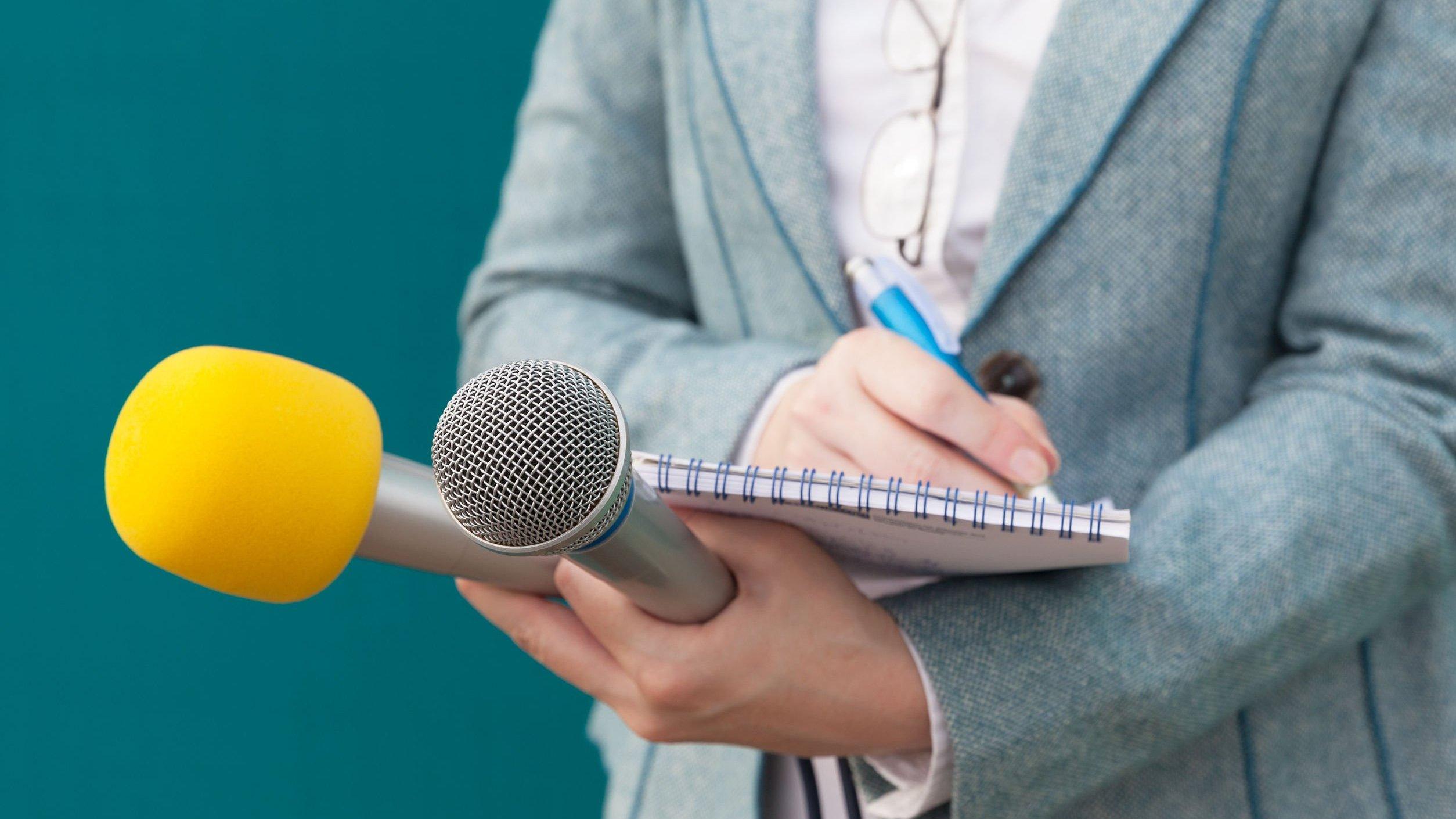 Profissional de relações públicas fazendo anotações enquanto segura microfone