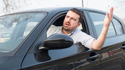 Homem em carro nervoso com expressão indignada