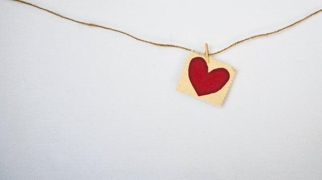 Pedaço de papel pendurado em corda e com coração desenhado