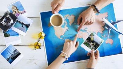 Mãos apontando para mapa mundi em mesa