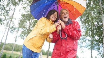 Casal abraçado dando risada ambos embaixo de um mesmo guarda chuva