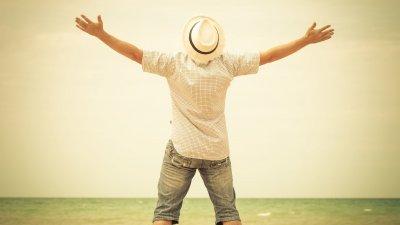 Homem de braços abertos em praia