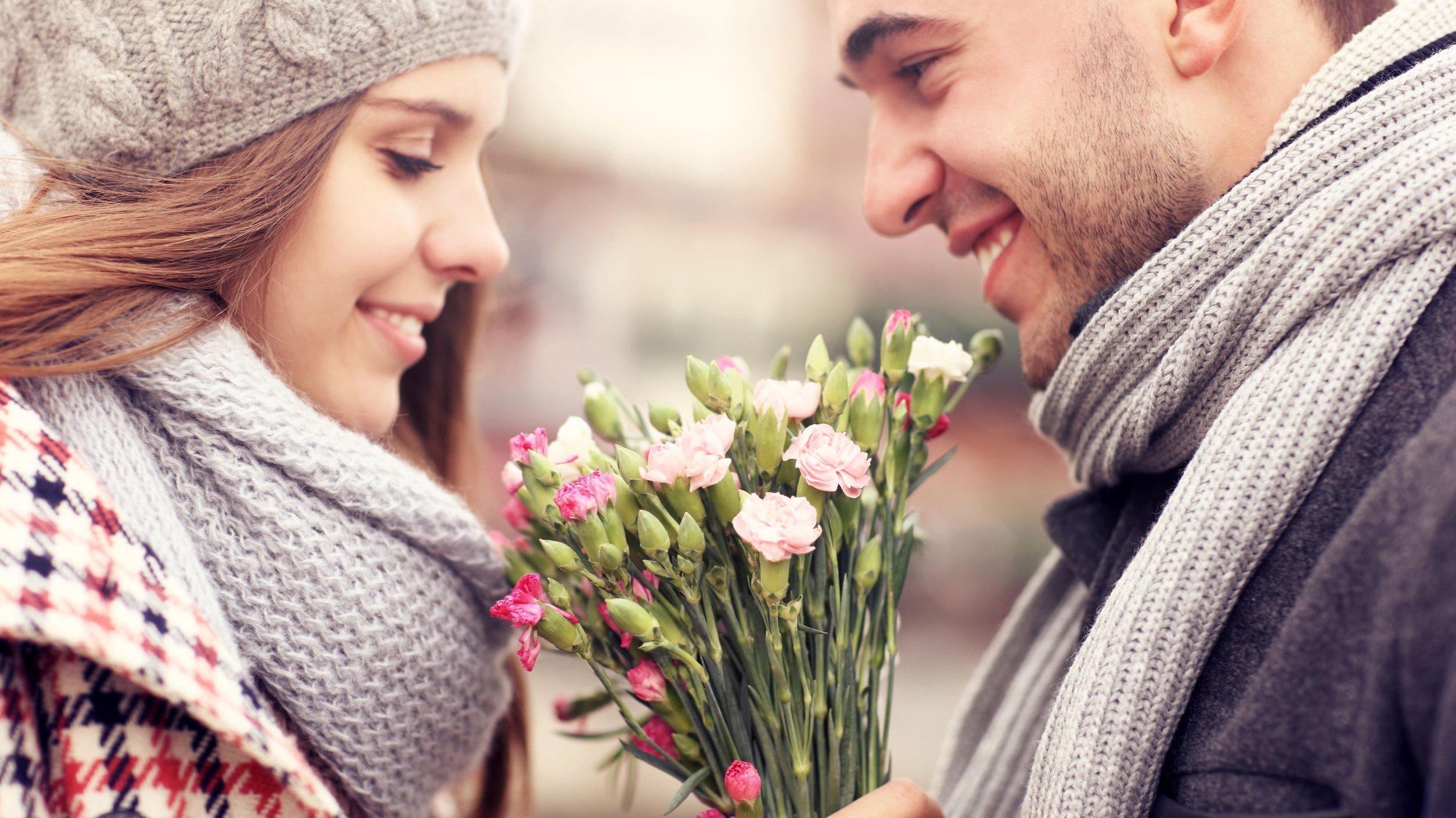 Homem entregando flores para mulher