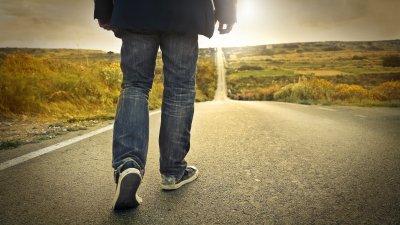 Homem caminhando em estrada