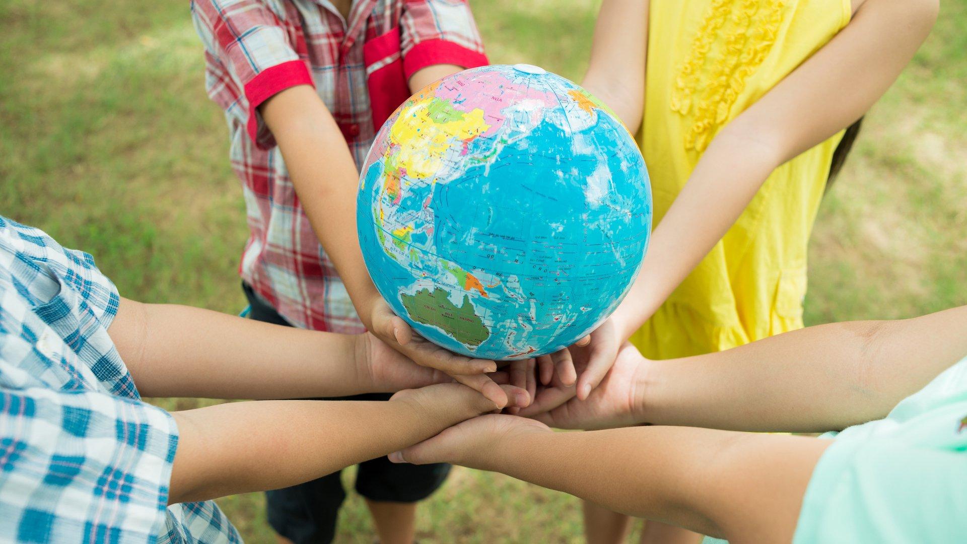 Crianças segurando o globo terrestre em suas mãos
