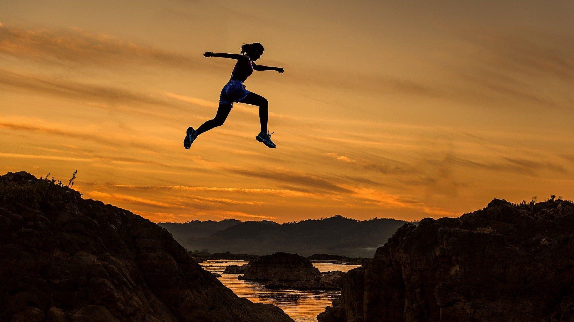 Silhueta de mulher saltando sobre um abismo de uma montanha para outra