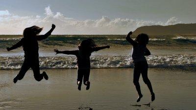 Silhueta de três pessoas pulando em praia
