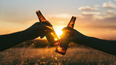 Pessoas brindando com cerveja em pôr do sol