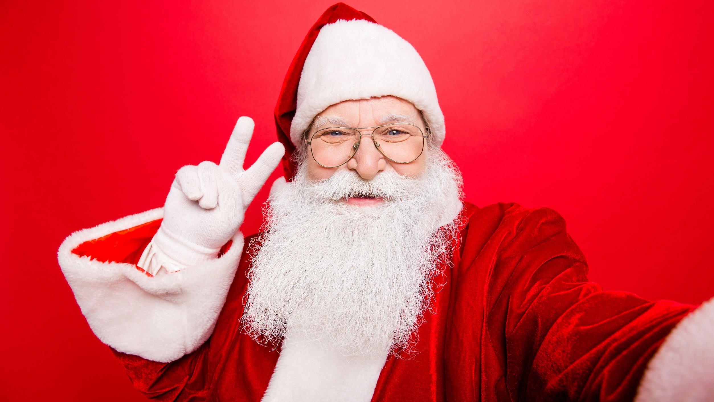 Papai noel fazendo sinal da paz com os dedos, tirando selfie