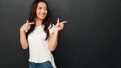 Mulher apontando com os dedos e sorrindo em frente de parede preta