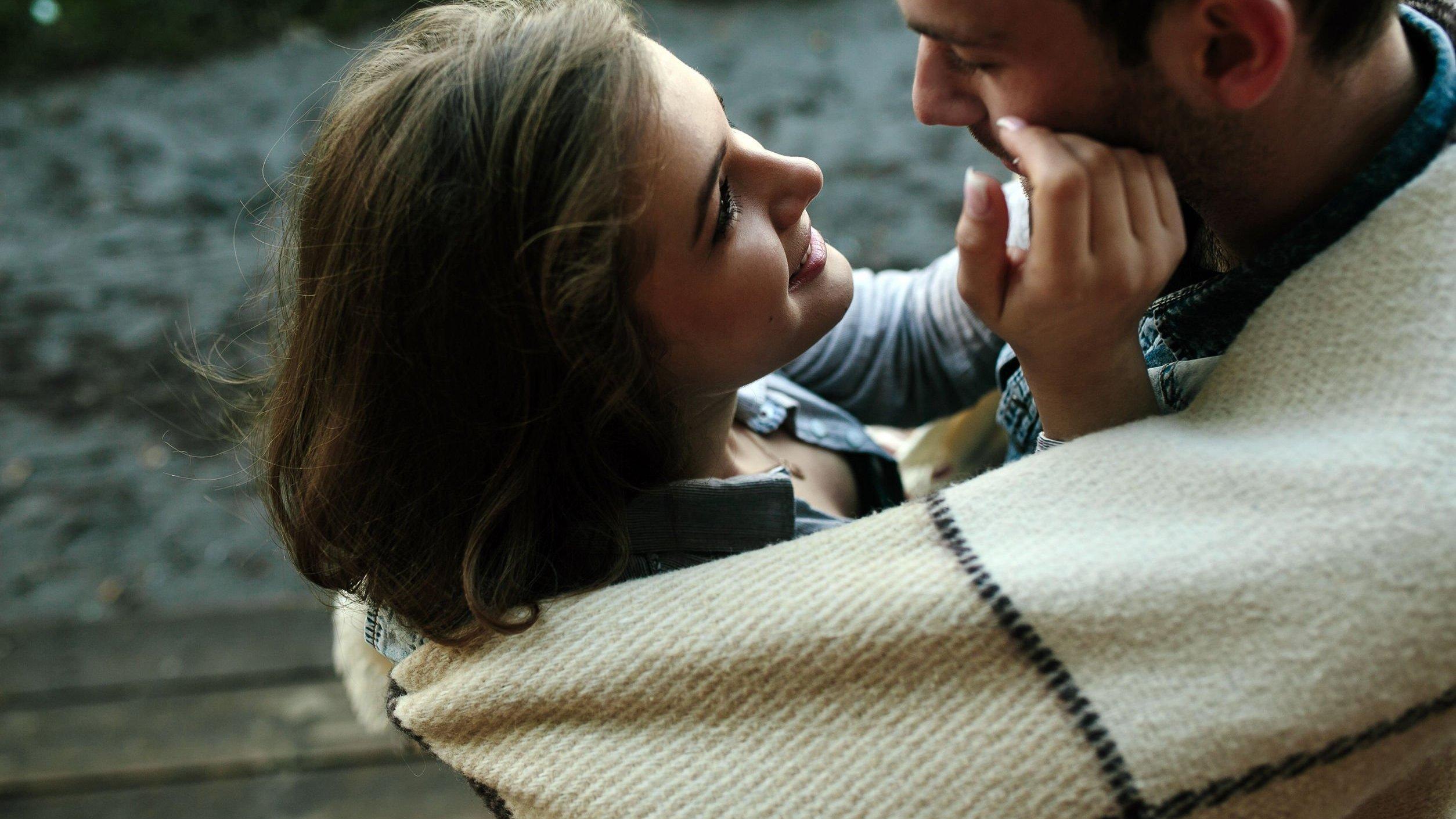 Casal se abraçando enrolados em cobertor