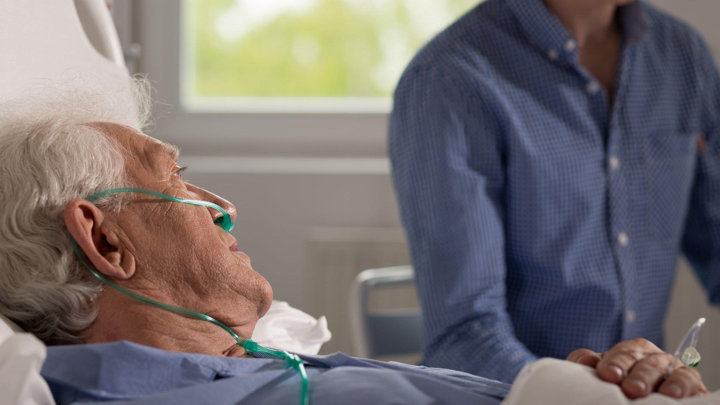 Idoso em hospital e homem ao lado
