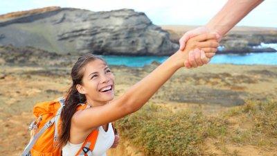 Mulher sorridente sendo puxada para cima com por uma mão