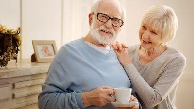 Casal de idosos sorrindo encostados em cômoda