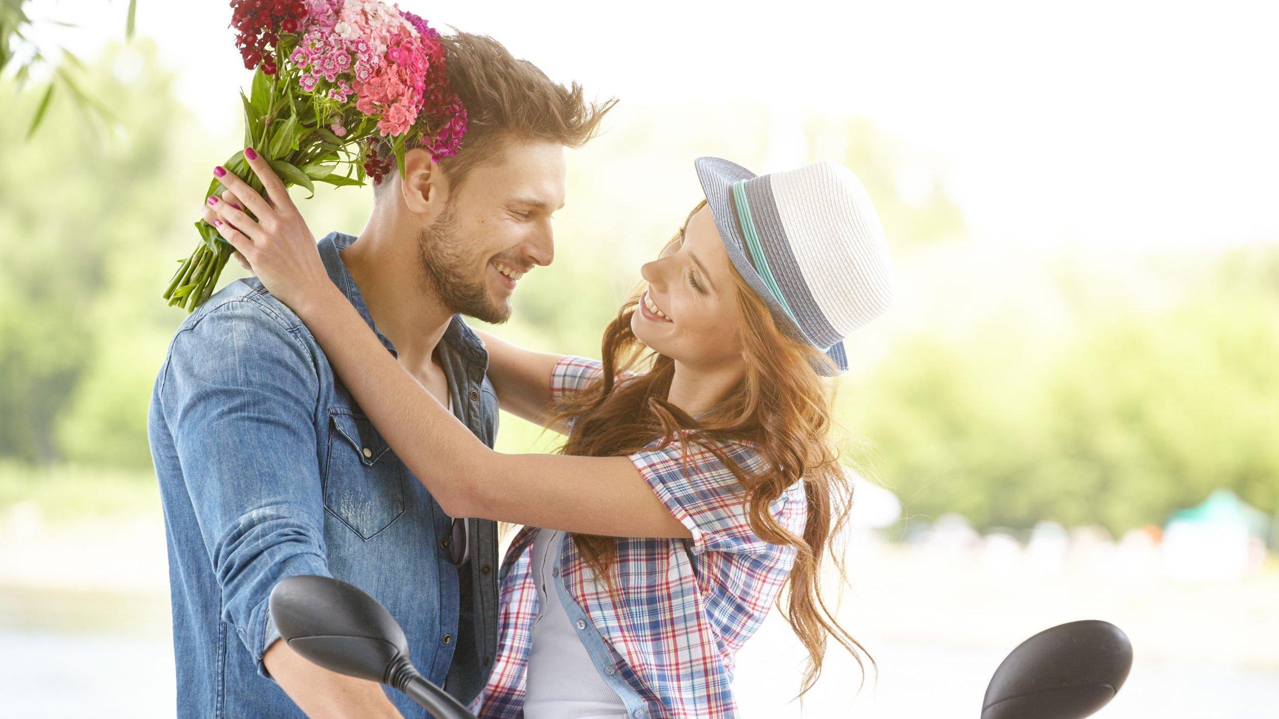 Mulher segurando buquê de flores rosas enquanto abraça homem