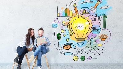 Homem e mulher mexendo em notebook ao lado de ilustrações coloridas que representam a criatividade