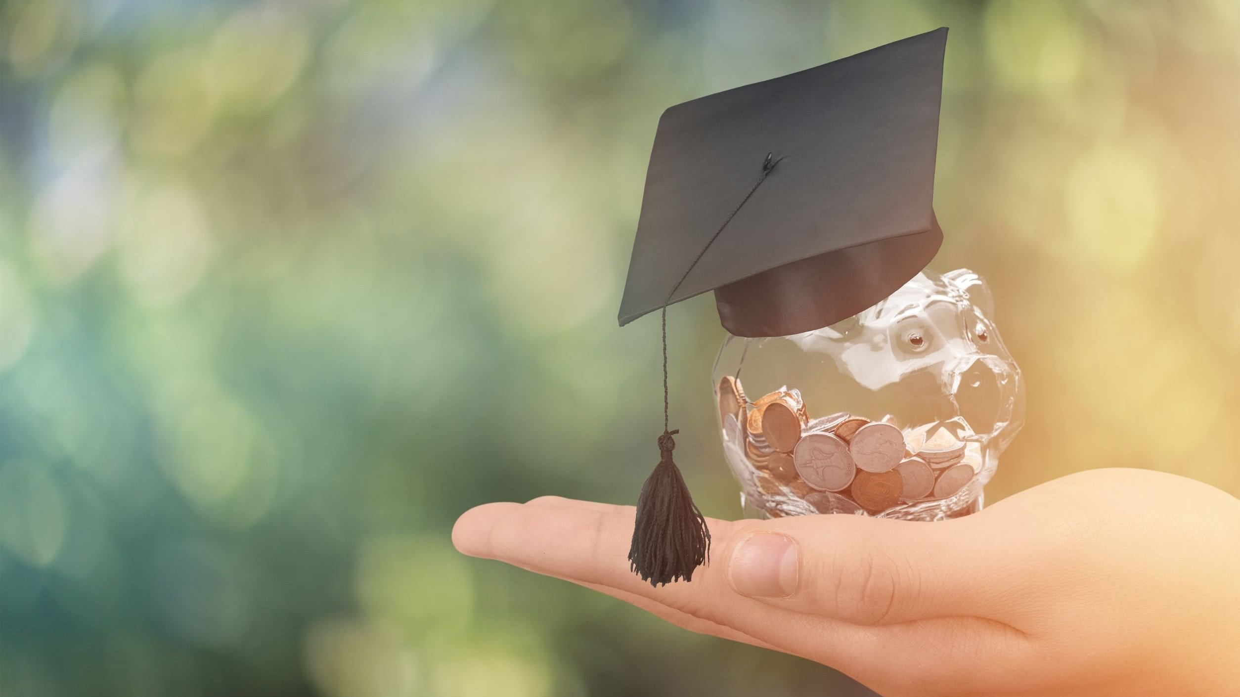Mão segurando cofrinho de vidro em formato de porco cheio de moedas com um capelo na cabeça