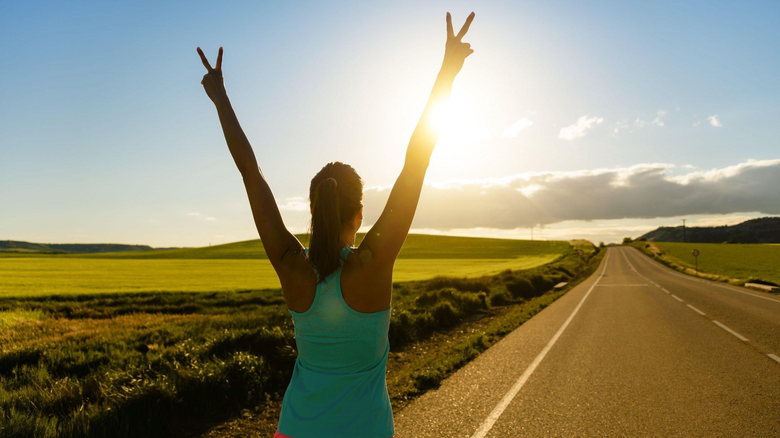 Mulher com braços pro alto fazendo sinal da paz, em estrada durante dia ensolarado