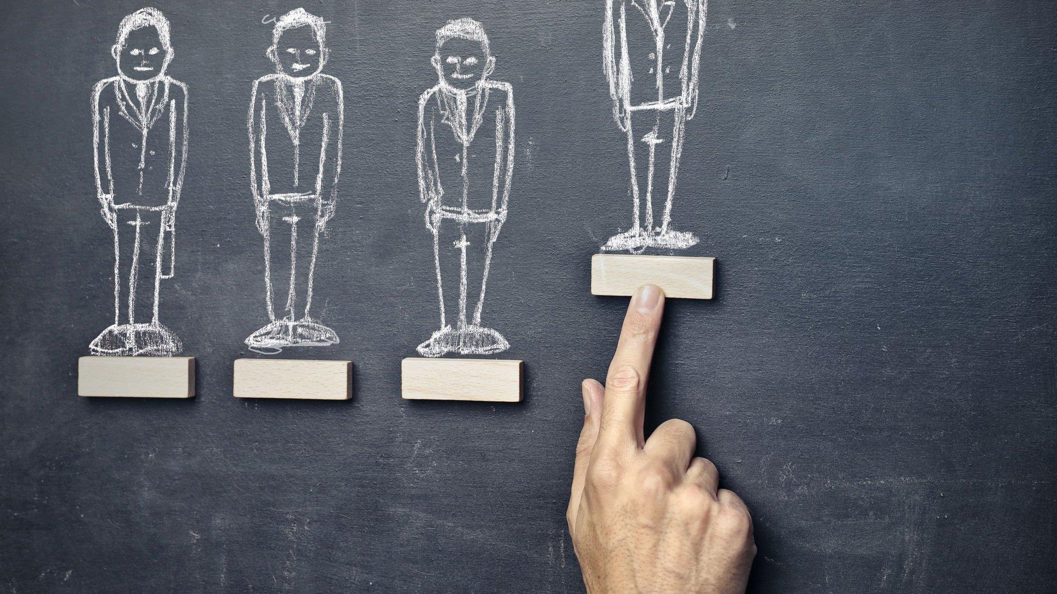 Lousa com diversos desenhos de pessoas, representando a desigualdade