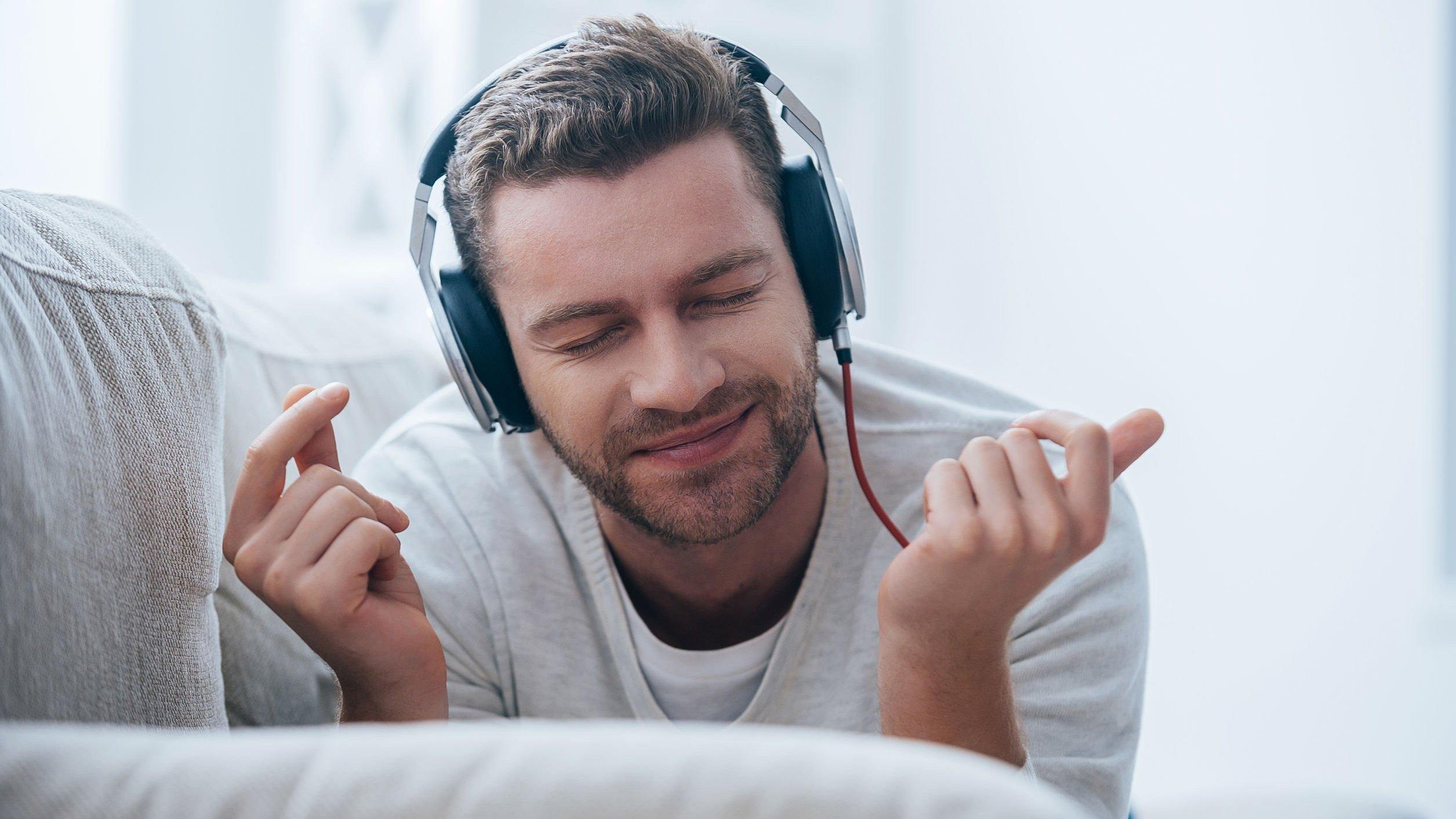 Homem deitado, com fones de ouvido, escutando música