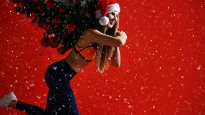Mulher sorrindo com goro de papai noel e segurando árvore de natal