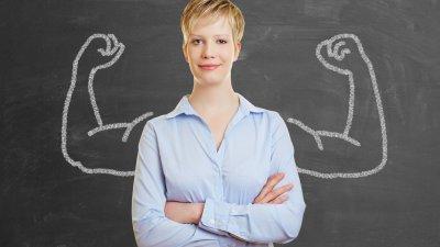 Mulher sorrindo, de braços cruzados, em pé em frente de lousa com desenho de braços fortes