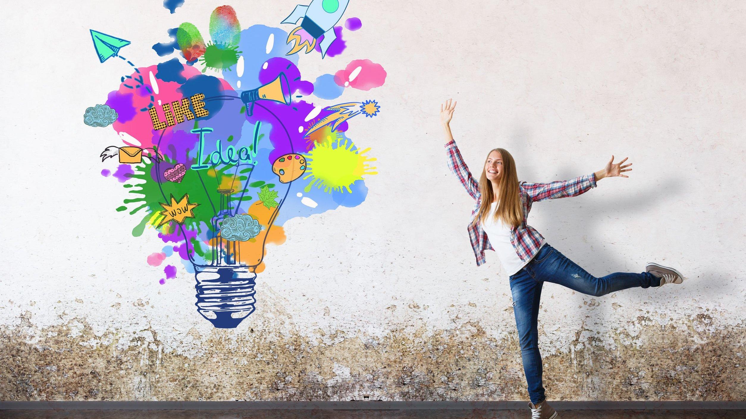 Mulher sorrindo em frente de parede com desenho de lâmpada colorida
